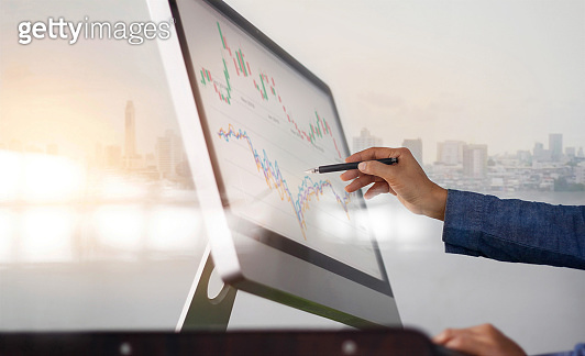Businessman and pen in hand analyzing sales data and economic growth graph on computer screen. Business strategy, stock market, Digital marketing.