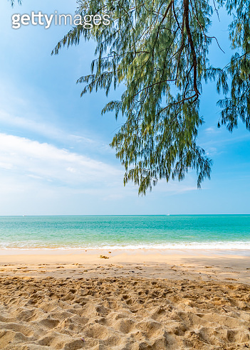 View from tropical beach at Koh Lanta island, Thailand. View to pure sea with boats and yacht on water. Look from shadow of tree on sand beach. Summer paradise, vibrant colors, tropical exotic place