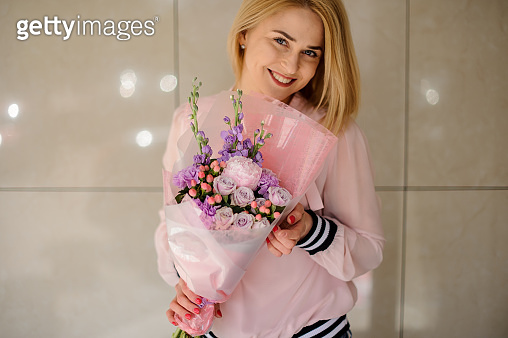Young blond woman holding big beautiful blossoming bouquet