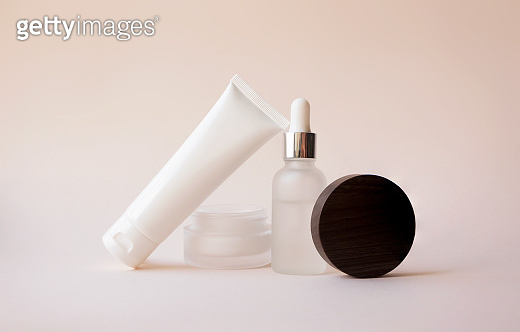 Body lotion in white plastic tube, open moisturizer cream in glass jar and liquid serum with dropper on beige background, front view. Balance concept. Branding beauty cosmetic products collection