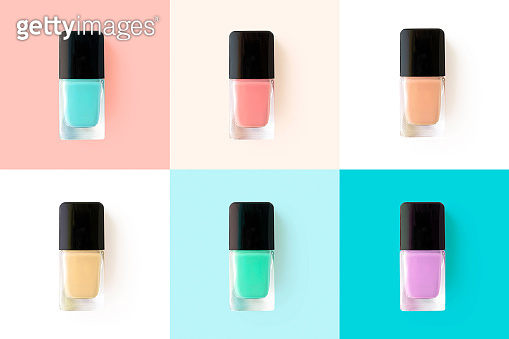 Nail polishes in glass bottles on bright colorful background, top view. Mockup fashion beauty products. Trendy flat lay manicure and pedicure