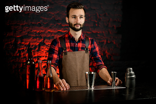 man in red shirt at bar prepares to make cocktail.