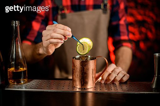 male bartender decorated metal cup by citrus slice.