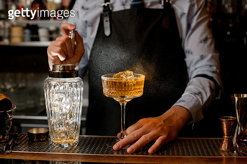 Barman in black apron sprinkles on glass with cocktail.