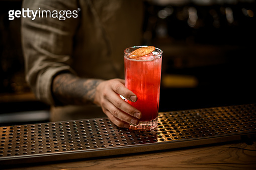 man's hand holds glass with cold drink with ice cubes, decorate with orange slice