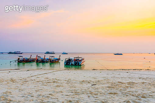 Magic sunset above small harbor with long tail boats at Ko Lipe island, Thailand. Tropical island is part of Tarutao national nature park. Soft light, concept of romantic evening in tropical paradise.