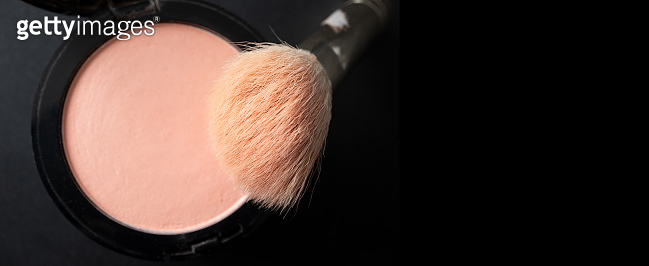 Makeup brush and peach blush with selective focus on black background horizontal banner format with copy space, top view. Decorative cosmetic product