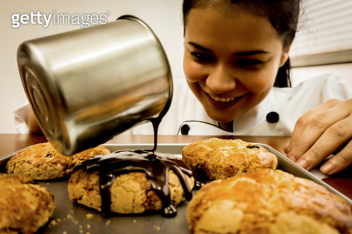 Young chef decorating cookies pouring hot chocolate over them while smiling