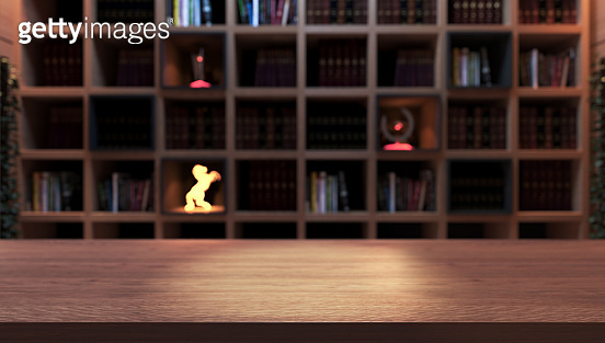Wooden empty desk front of black bookshelf with modern and classic books from library deep of field effect