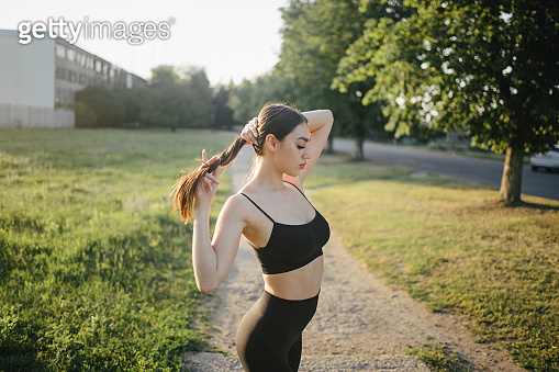 Young woman in activewear exercising outdoors