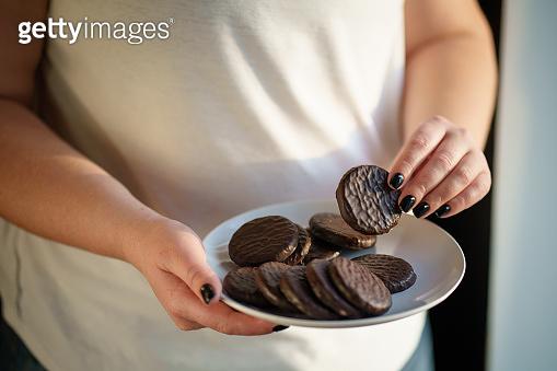 diet breakdown. overweight woman eating sweets