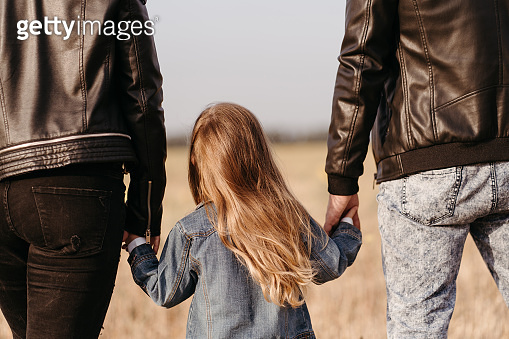 Mother, father and daughter walking holding hands