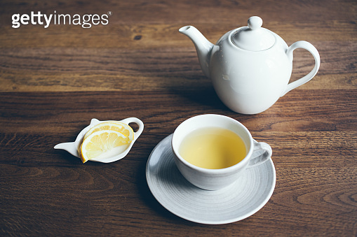 Close-up shoot of cup of hot tea with lemon and infusion teapot on brown wooden table.