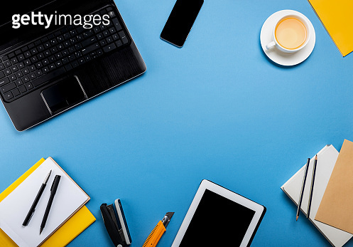Online work or education concept. Laptop, tablet computer, smartphone, notepad, book, stationery on the blue background. Top view with copy space.