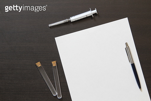 Template of white paper with pen and syringe for injection on dark wenge color wooden background