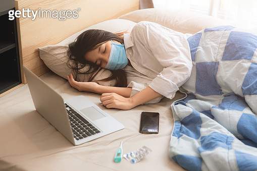 Asian girl teen sick illness lay on bed wearing face mask with laptop computer.