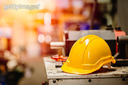 yellow helmet hardhat safety for factory worker working in danger workplace with space for text.
