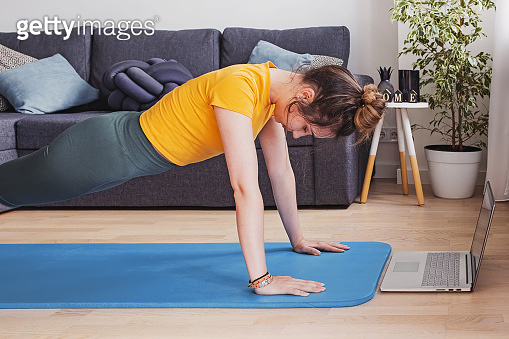 Young woman doing yoga at living room