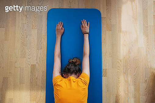 Young woman doing yoga at living room.