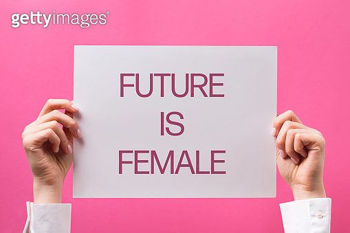 Woman's hands holding poster with text Future is female.