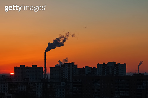 Yellow sunset over industrial landscape with factory chimneys and pipes