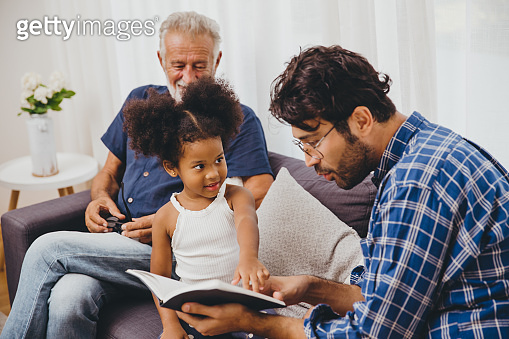 Clever genius kid little girl hand pointing at content at the book to teaching her parent.