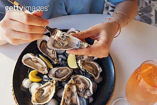 Woman eating fresh oysters with lemon close-up.