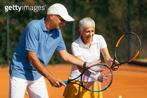 Tennis Instructor with Senior Woman on Clay Court. Woman having a Tennis Lesson.