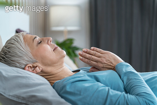 Meditation Before Sleeping.  Beautiful Mature Woman Lying in Bed and Meditating with her Eyes Closed