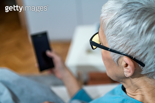 Mature Woman Using Blue-Light Blocking Glasses in the Evening to Minimize Sleep Disruption