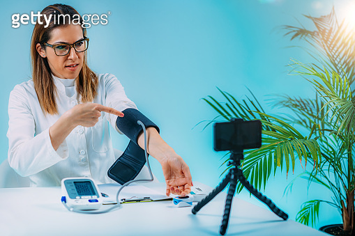 Telehealth – Medical doctor recording video instructions for patient and demonstrating how to measure blood sugar