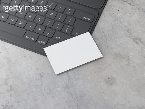 White Business Card Mockup on black digital tablet keyboard on concrete table