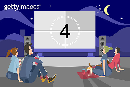 People watching movie outdoors in evening