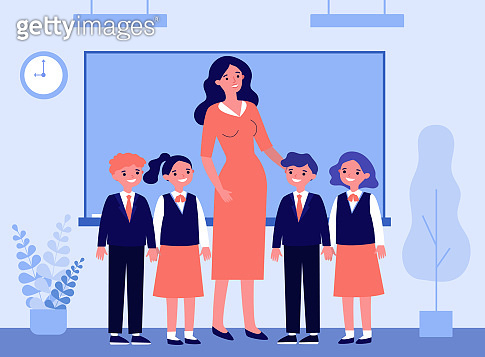 Happy children and teacher standing together in classroom