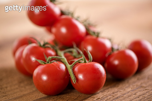 red ripe vine tomatoes on the vine on vintage old wooden background