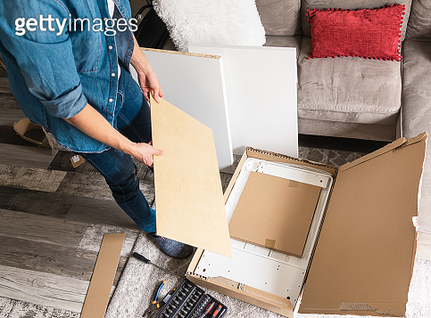 Young man unpacking box with DIY furniture for home