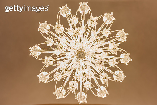 chandelier lit on ceiling in shape of a snowflake