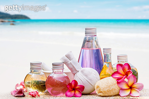 aroma essential oil or spa and natural fragrance oil with dry flower over blurred tropical summer beach background
