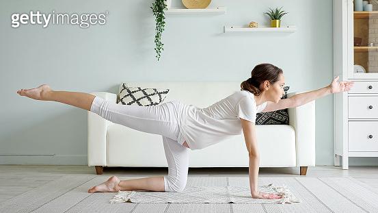 Pregnant woman does vyagrasana practicing yoga at home