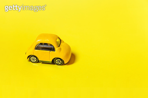 Simply design yellow vintage retro toy car isolated on yellow background. Automobile and transportation symbol. City traffic delivery concept Copy space