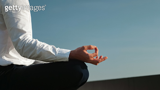 man in white shirt and black pants meditates under clear sky