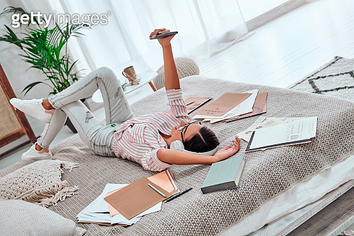Young woman lying on the bed with laptop and phone. Resting after the work