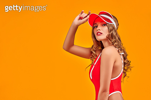 Attractive tanned girl posing in red visor, isolated on orange