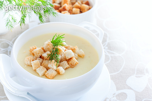 Mashed potato soup with homemade croutons of white bread in a white soup plate, horizontal, copy space
