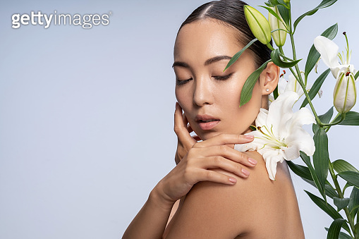 Tender Asian lady posing with beautiful bouquet in studio