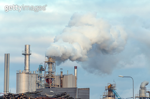 Woodworking plant, thick smoke from the pipes against the gray-blue sky. Environmental pollution.