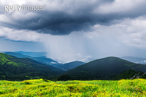 Amazing flowing rainy clouds in evening mountains