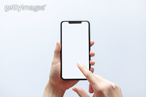 Smartphone mockup. Hand holding black phone white screen. Isolated on white background. Mobile phone frameless design concept.