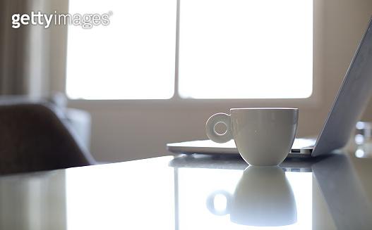 White coffee mug beside laptop computer