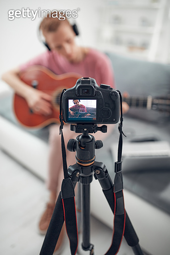 Guitarist making video lessons and tutorials for internet vlog website classes.